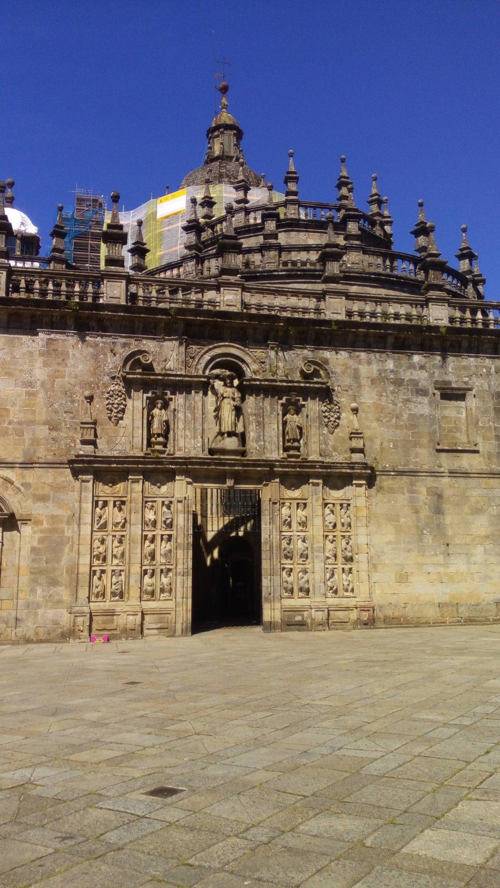 La Puerta Santa enmarcada por 24 estatuas recuperadas del coro románico del Maestro Mateo, en el S. XVI. En su parte superior las esculturas que representan a Santiago y a sus discípulos Atanasio y Teodoro