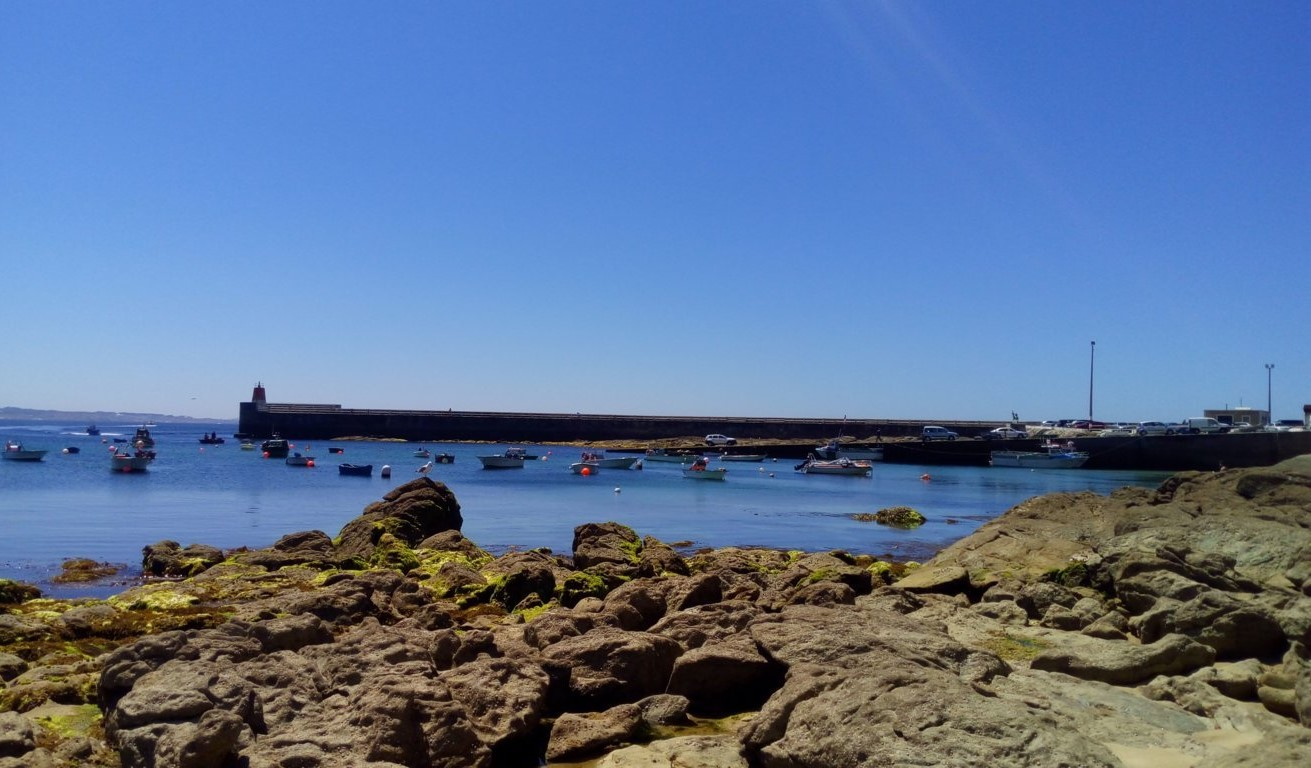 Al fondo - muelle del puerto de Corrubedo